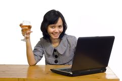 Business Woman Celebrating Her Success with Wine. Beautiful asian business woman celebrating her success with wine in front of her computer Stock Photo