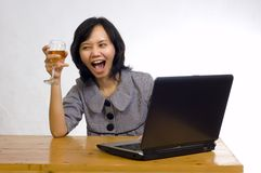 Business Woman Celebrating Her Success with Wine. Beautiful asian business woman celebrating her success with wine in front of her computer Stock Photos