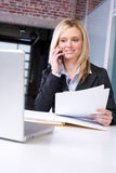 Business Woman on cell at desk. In modern office Stock Photo