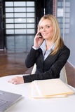 Business Woman on cell at desk Royalty Free Stock Photos
