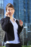 Business Woman on Cell Phone. Over business center building on the back Royalty Free Stock Photography