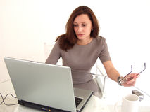 Business Woman and cell phone. Business Woman on notebook PC, with cell phone and coffee cup and holding glasses Stock Photos