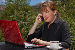 Business woman on cell phone working. Business woman sitting at an outdoor table talking on her cell phone and typing on her laptop Stock Photos
