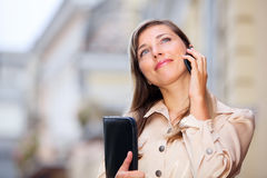 Business woman with cellphone. Beautiful lady using cellphone and holding folder with copy space Royalty Free Stock Photography