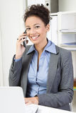 Business woman with cellphone. Smiling business woman with cellphone at workplace Stock Photo