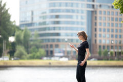 Business woman on cellphone in the street. Portrait of young confident business woman using cellphone app, messaging on the street in front of blue glass modern Stock Images