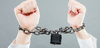 Business woman with chained hands. Crime, arrest jail or business concept. Closeup woman with chained hands on grunge background Stock Photography