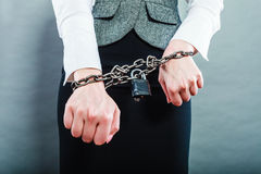 Business woman with chained hands. Crime, arrest jail or business concept. Closeup woman with chained hands on grunge background Royalty Free Stock Image
