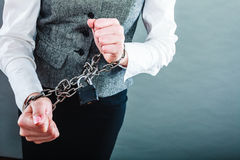 Business woman with chained hands. Crime, arrest jail or business concept. Closeup woman with chained hands on grunge background Stock Photo