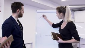 Business woman charting on blackboard for male colleagues in office. stock footage