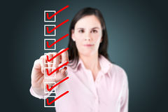 Business woman checking on checklist boxes. Royalty Free Stock Image