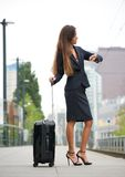 Business woman checking time at train station Stock Photography