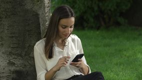 Business woman checks her phone sitting under the tree in park.  stock video footage