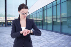 Business woman checks time on her wrist watch standing on street Royalty Free Stock Photography