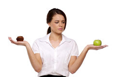 Business woman choosing between cake and fruit Royalty Free Stock Image