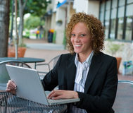Business Woman In The City 9. Smiling young business woman working on a laptop computer at a sidewalk cafe Royalty Free Stock Photos