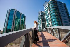 Business woman in city business center stand on bridge. Young business woman in city business center stand on bridge Stock Image
