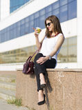 Business woman in the city. Woman enjoying coffee outside the office building Stock Photo