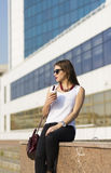 Business woman in the city. Woman enjoying coffee outside the office building Stock Photos