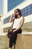 Business woman in the city. Woman enjoying coffee outside the office building Royalty Free Stock Image