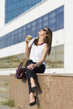 Business woman in the city. Woman enjoying coffee outside the office building Stock Photography