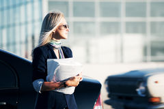 Fashion business woman with financial papers next to car