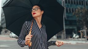 Business woman on city street with umbrella. Young business woman walking on city street with umbrella. Asian female business professional with umbrella walking Stock Images