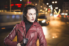 Business woman on a city traffic bokeh background. Casual girl in a leather jacket walks in night city market street Royalty Free Stock Photos