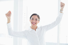 Business woman with clenched fists at office. Successful young business woman with clenched fists at office Royalty Free Stock Image