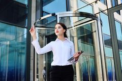 Business woman clicks with an index finger on a virtual screen on the background of an office building stock image