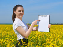 Business woman with clipboard point on paper in flower field outdoor. Young girl in yellow rapeseed field. Beautiful spring landsc Royalty Free Stock Photos