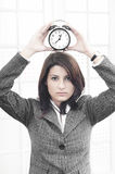 Business woman with a clock. Business woman holding a clock on her head with the abstract meaning that time is passing Stock Images