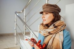 Business woman in coat stands on the stairs in the mall with smartphone. Shopping. Fashion royalty free stock photos