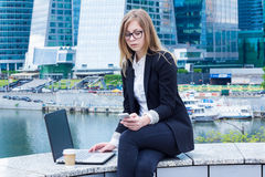 Business woman on coffee break with a laptop and writing a message on the background of skyscrapers Royalty Free Stock Photography