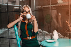 Business woman at coffee break talking phone and drinks tea. Business concept. Business woman in a cafe. business after hours Royalty Free Stock Photography