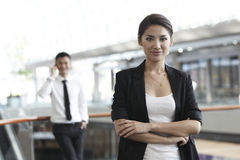 Business woman with colleague in the background Royalty Free Stock Photos