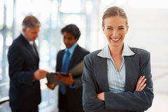 Business woman with colleagues at the back Royalty Free Stock Photos