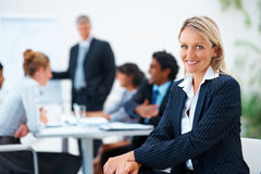 Business woman with colleagues at the back Stock Photos