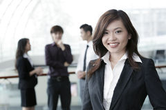 Business woman with colleagues in the background Stock Image