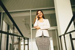 Business woman on stairs. Business woman coming down the stairs and talking on cell phone Stock Image