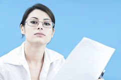 Business woman communicating. Young business woman communicating something from a paper, looking arrogant and selfconfident focus selected on the face Stock Image