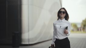 Woman have a call with her luggage at the airport. Business woman on commute carries a passport and plane or train tickets. while walking with hand luggage in stock footage