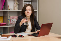 Business woman at the computer holding a glass of water Stock Images