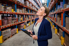 Business woman is concentrating during her work. In a warehouse royalty free stock images