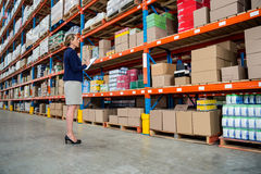 Business woman is concentrating during his work. In a warehouse royalty free stock images