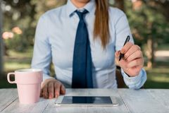Business woman concept with mobile phone. Business concept with female business person sitting by the table and holding. Business concept with female business stock image