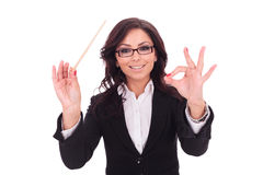Business woman conducts smilingly. Young business woman conducts with a baguette and a smile . on white background stock image