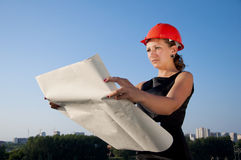 Business woman considers construction plans. Blue sky background Stock Photos