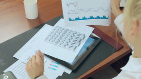Business woman considers graphs and data on paper stock footage