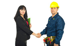 Business woman and  constructor worker deal. Business woman and constructor worker make a deal and shaking their hands isolated on white background Stock Image